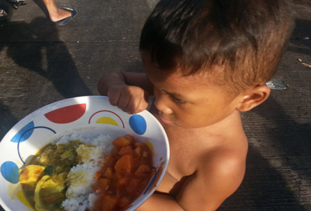 A Young Boy Accepts A Nourishing Meal in the Philippines
