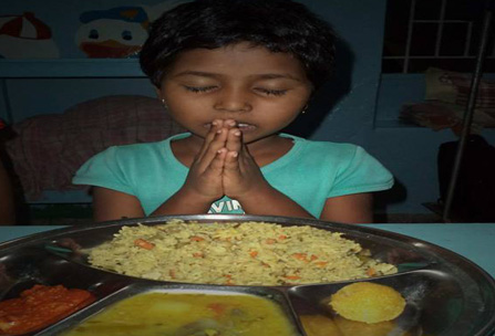 A Hungry Girl Prays In Gratitude for A Hot Meal at Neura HoPE Learning Center in Goa, India